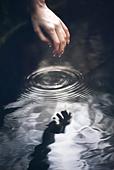hand going into water - Stock Image - BRHEMK