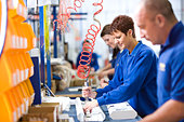People working on aluminium light fittings on production line in factory - Stock Image - BN1XJW