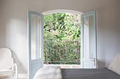 French doors open to balcony in luxury bedroom - Stock Image - E17PBF