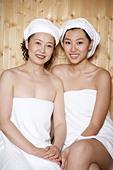 Women Sitting In Sauna Wearing Towels - Stock Image - BAM14C