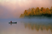 Canoeing on misty morning Quetico Provincial Park Ontario Canada - Stock Image - B9W1WJ