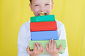 Boy eating snack on top of lunch boxes - Stock Image - A2TPHT