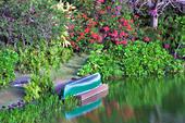 Pond with canoe and garden at Na Aina Kai Botanical Gardens. Kauai, Hawaii - Stock Image - BE5M1C