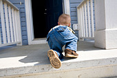 Child crawling towards open door - Stock Image - B7X17X