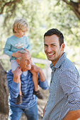 Three generations of men relaxing outdoors - Stock Image - CNMF93