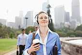 Businesswoman listening to headphones carrying coffee - Stock Image - DYF7D8