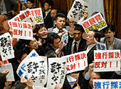 Tokyo, Japan. 15th July, 2015. Opposition lawmakers surround Yasukazu Hamada (2nd, R), chairman of the lower house special committee on security legislation, in Tokyo, Japan, on July 15, 2015. A series of controversial security-related bills proposed by Japan's ruling bloc were rammed through a special committee of Japanese parliament's lower house Wednesday noon, paving the way for a vote for the bills at the full chamber later. © Ma Ping/Xinhua/Alamy Live News - Stock Image - EXKPJP