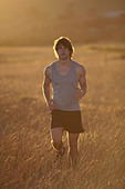Man running in tall grass at sunset - Stock Image - D2A9RP