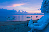 Indonesia, Bali, Sanur, Statue with sea in background at dusk - Stock Image - CR74N3