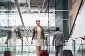 Businesswoman with suitcase walking at airport - Stock Image - DA4WX4