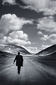 a man walking down an open road - Stock Image - A310CH