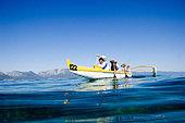 Five Women Paddling a Canoe on Lake Tahoe, California - Stock Image - BA8HCD
