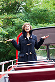 Exuberant woman standing with arms outstretched on double decker bus - Stock Image - CC9FYK