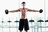 Man lifting weights in gym - Stock Image - CR020J