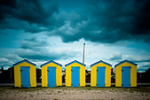 Yellow and Blue beach huts under a moody sky on Littlehampton beach, West Sussex - Stock Image - BK9NW6