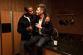 Gay couple drinking wine in kitchen - Stock Image - CTH10N