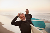 Older surfers carrying boards on beach - Stock Image - D2XGHD