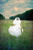 a woman is running with a wedding dress over a field of flowers - Stock Image - CTJK38