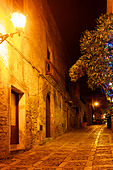 Cobblestone street illuminated by light at night. - Stock Image - D1326P