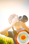 A Young boy, aged 7, using a digital SLR camera in a sunny garden. - Stock Image - CBH1KA