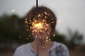 Thirteen year old boy holds up a large spakler on the fourth of July. - Stock Image - CTWJH3