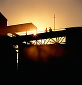 Workers silhouetted against the sunrise at a cement plant. - Stock Image - B1TEHD