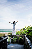 Mature woman with arms open on top of walkway railing, Juno Beach, Florida, USA - Stock Image - EKHE97