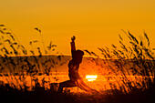 Billingham, UK. 26th September, 2014. UK Weather:  Female jogger stretching at sunrise on a breezy but mild Friday in north east England. © ALANDAWSONPHOTOGRAPHY/Alamy Live News - Stock Image - E7XWT9