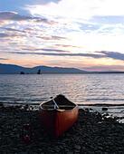 canoe by Maine lake at sunset - Stock Image - E9YT3Y