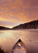 Canoe on Boggy Lake at sunset, Alberta, Canada. - Stock Image - CFAC18
